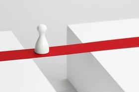 Spielfigur balanciert über rotes Band