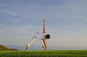 sportliche Frau auf Feld in Yoga Position