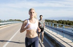 sportliches Paar joggt auf Brücke über Gewässer