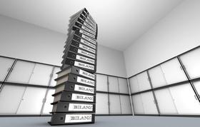 """Stapel von Aktenordnern mit Aufschrift """"Bilanz"""" vor Aktenschränken"""