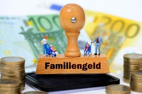 Miniaturfiguren auf einem Stempel mit der Aufschrift Familiengeld mit Geld und Geldscheinen