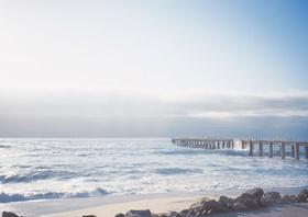 Strand mit langem Steg ins Meer