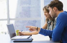 Student und Studentin sitzen vor Laptop und Bücher