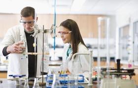 Studenten im Labor mit Schutzkittel und Schutzbrille