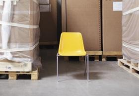 Stuhl steht zwischen Paletten mit Kartons