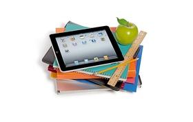 Tablet liegt auf Notizblöcken und Laptop