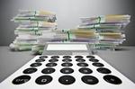 Taschenrechner frontal mit Geldscheinstapeln im Hintergrund