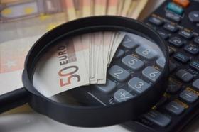 Taschenrechner und 50-Euro-Scheine unter einer Lupe