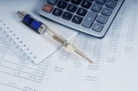 Taschenrechner und Kugelschreiber liegen auf Rechnungen