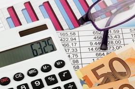 Taschenrechner vor Bilanzen, Geld und Lesebrille