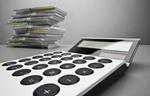 Taschenrechner vor Stapel aus Geldscheinen