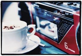 Tasse Cappuccino steht neben Radiorecorder