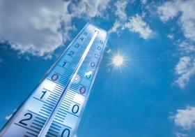 Thermometer vor blauem Himmel und Sonne