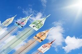 Papierflieger aus Geld steigen in den Himmel