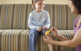 Tochter lächelt Mutter an während diese ihr Pflaster auf Knie klebt