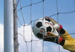Torwarthaende halten Fussball vor Netz