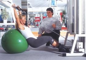 Trainer gibt Frau im Fitnessstudio Anleitung beim Training