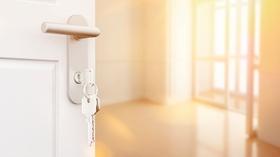 Offene Tür mit Schlüssel im Schloss in einer neuen Wohnung