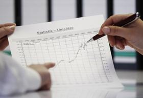 Umsatzstatistik Blatt mit Kurve und zwei Hände
