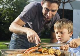 Vater mit Sohn beim Grillen