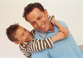 Vater mit Sohn huckepack auf dem Ruecken