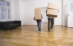 Vater und Sohn tragen Umzugskartons in Wohnung