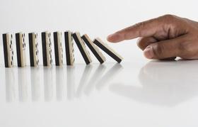Hand bringt ersten Dominostein in Reihe zum umfallen