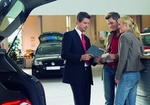 Verkäufer mit Pärchen im Autohaus