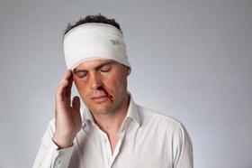 Verletzter Mann mit Kopfverband, Nase blutet