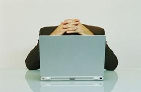 Verzweifelter Mann hinter Laptop