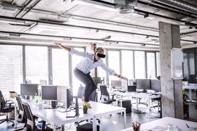 Virtual Reality VR Mann tanzt auf Bürotisch