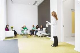 Wartezimmer mit mehreren Leuten und Ärztin
