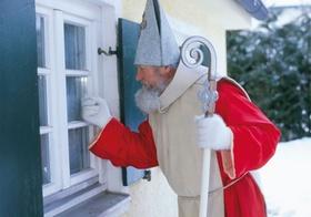 Weihnachtsmann klopft an Hausfenster