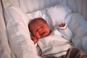 Weinendes Baby in Bettchen