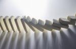 Weiße Dominosteine fallen nacheinander um