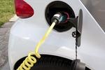 weißes Auto mit Stromstecker in der Tanköffnung