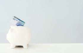 Weißes Sparschwein mit eingestecktem 20 Euro Schein