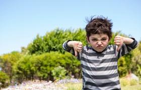 Wütend aussehender kleiner Junge zeigt Daumen nach unten