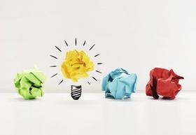 zerknüllte Papierkugeln in verschiedenen Farben mit Glühbirne