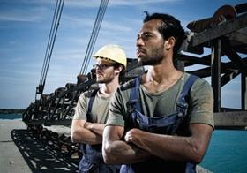 Zwei Arbeiter stehen in Kieswerk vor Stahlkonstruktion, Foerderband