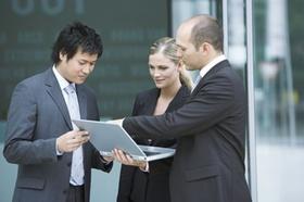 Zwei europäische und ein asiatischer Mitarbeiter schauen gemeinsam auf Laptop-Monitor