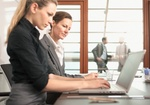 Zwei Frauen arbeiten an Laptop