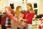 Zwei Teenager-Maedchen im Kaufhaus, suchen Kleidung aus