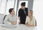 Zwei Frauen und ein Mann im Büro an Schreibtisch, Besprechung