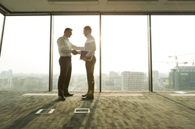 zwei Geschäftsmänner schütteln sich in hellem Büro die Hände