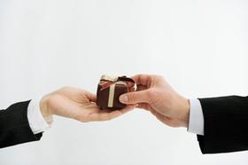 Zwei Hände im Bild, eine Hand überreicht der anderen ein kleines Geschenk