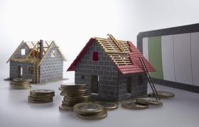 Zwei Hausmodelle mit teilweise fertiggestelltem Dach und Münzen