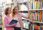 Zwei jugendliche Schuelerinnen in Bibliothek