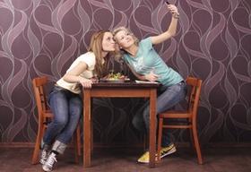 Zwei junge Frauen sitzen an Tisch in Bistro, fotografieren sich mit Handys, Selfie