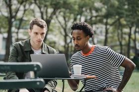 Zwei junge Männer schauen im Freien in einen Laptop